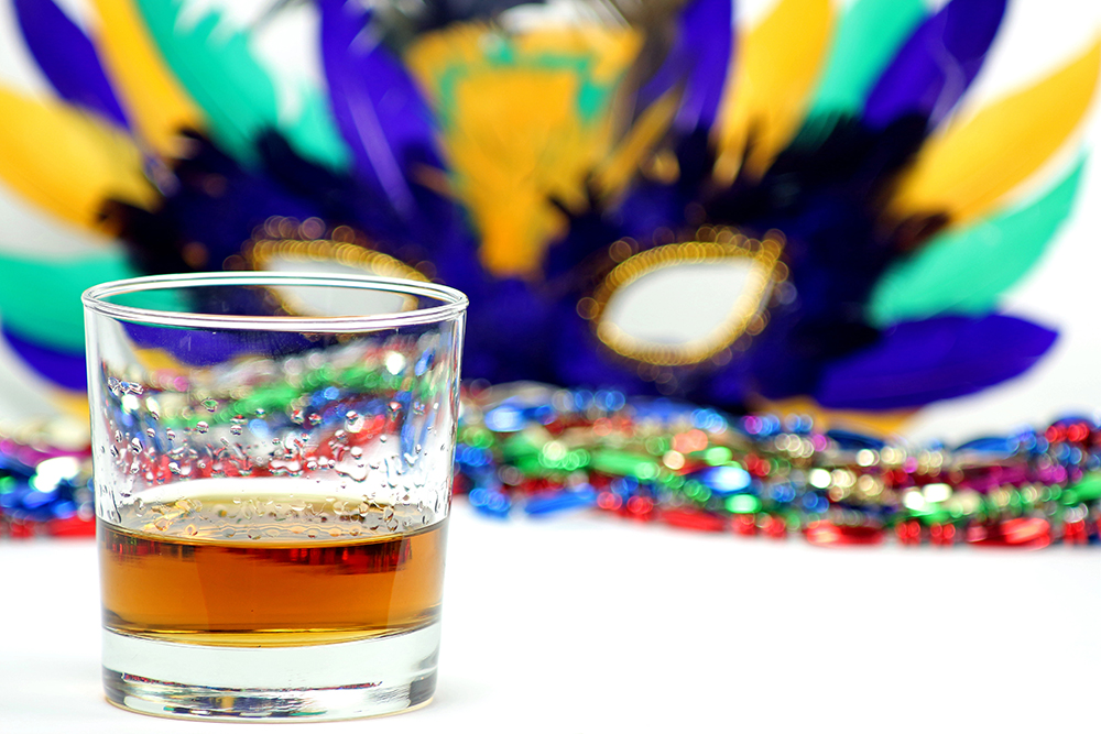 A glass with a shot of whiskey is the focal point in this photo. Soft focus in the background is colorful Mardi Gras beads and a feather mask.
