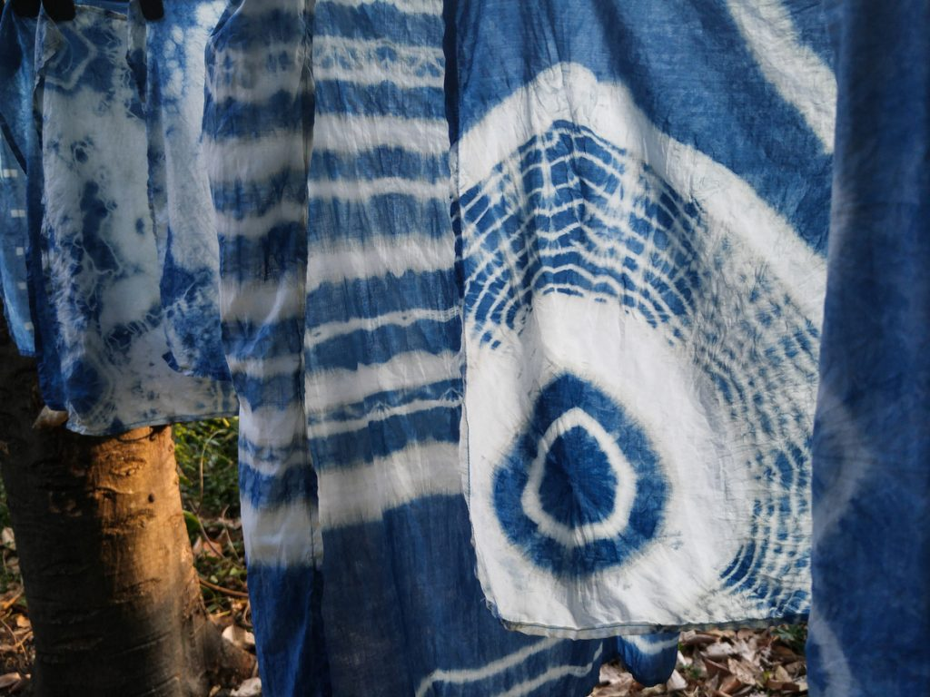 Beautiful natural indigo tie dye fabric with garden view in background.